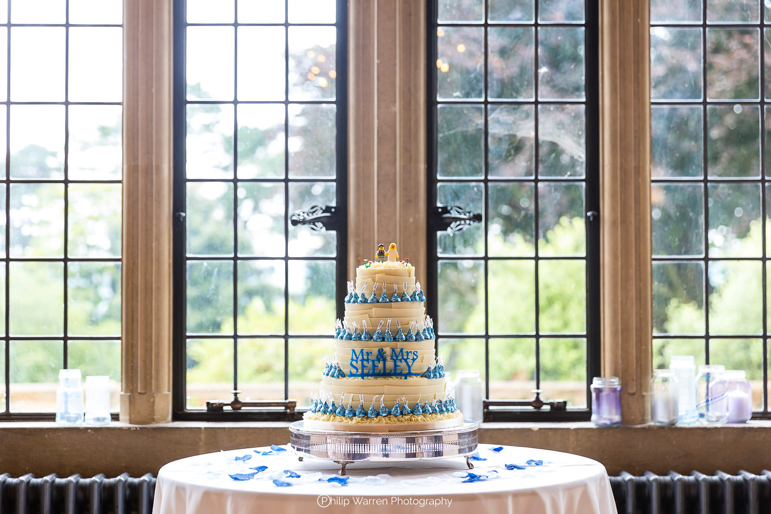 white and blue wedding cake on table in window