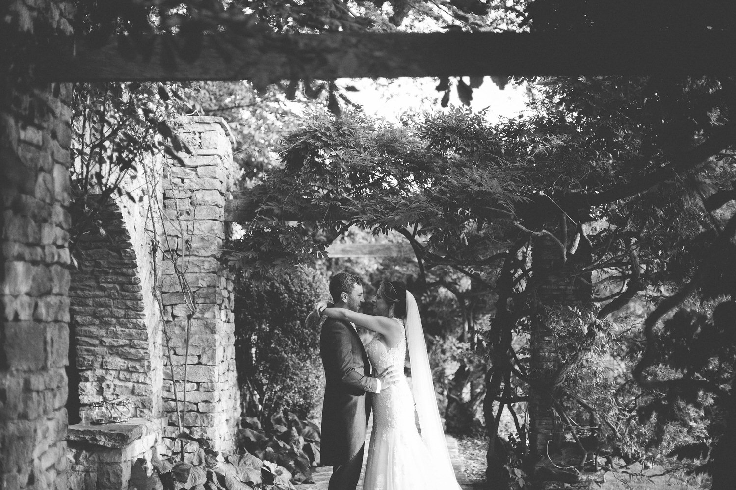 bride and groom holding each other in glenfall house gardens