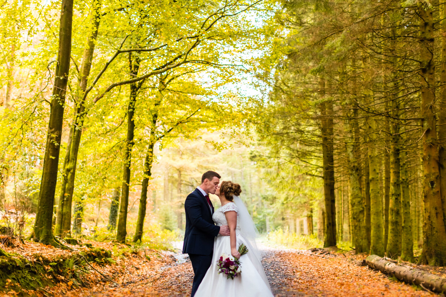 kissing in the forest for these wedding photos