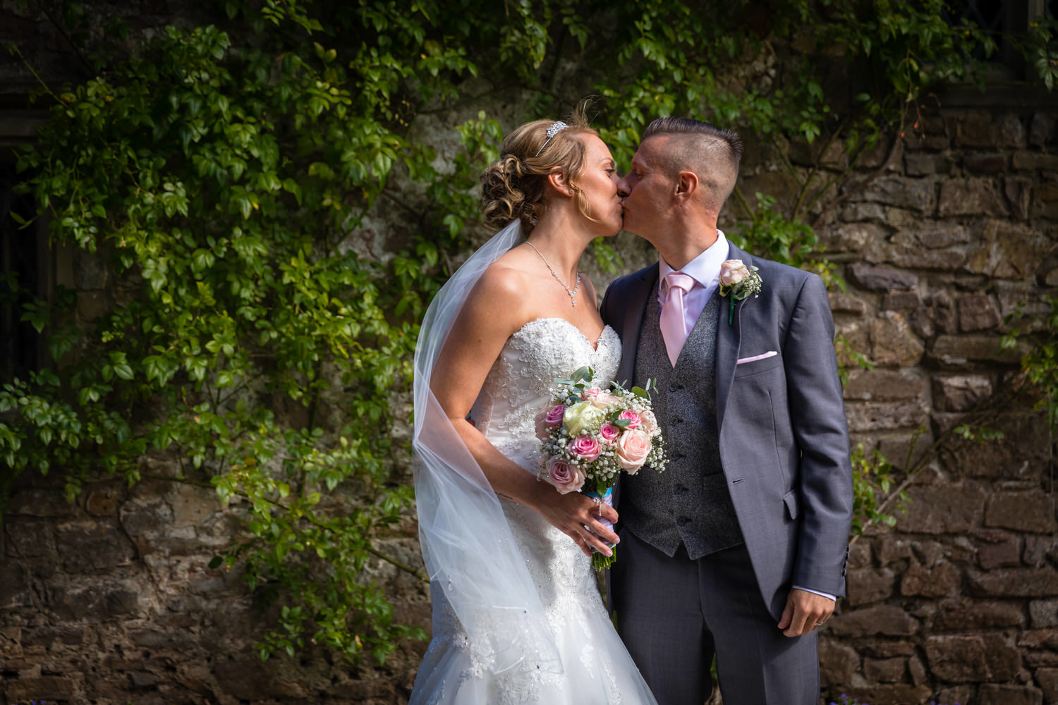 kissing bride and groom at miskin manor