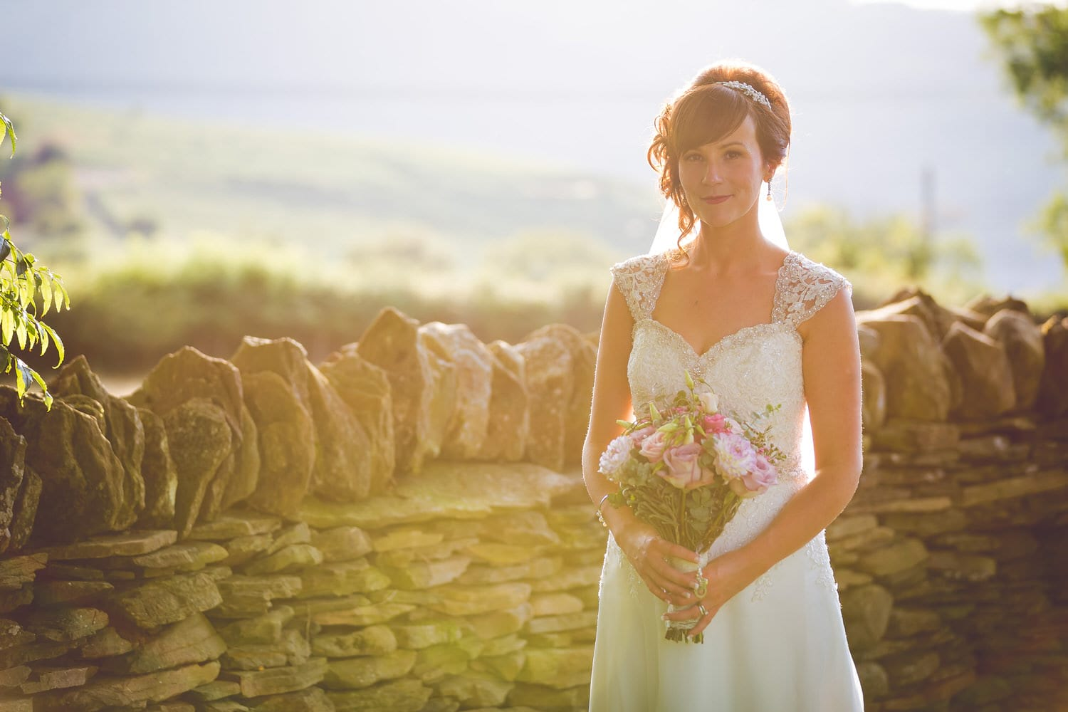 bride holding flowers in the grounds of llechwen hall