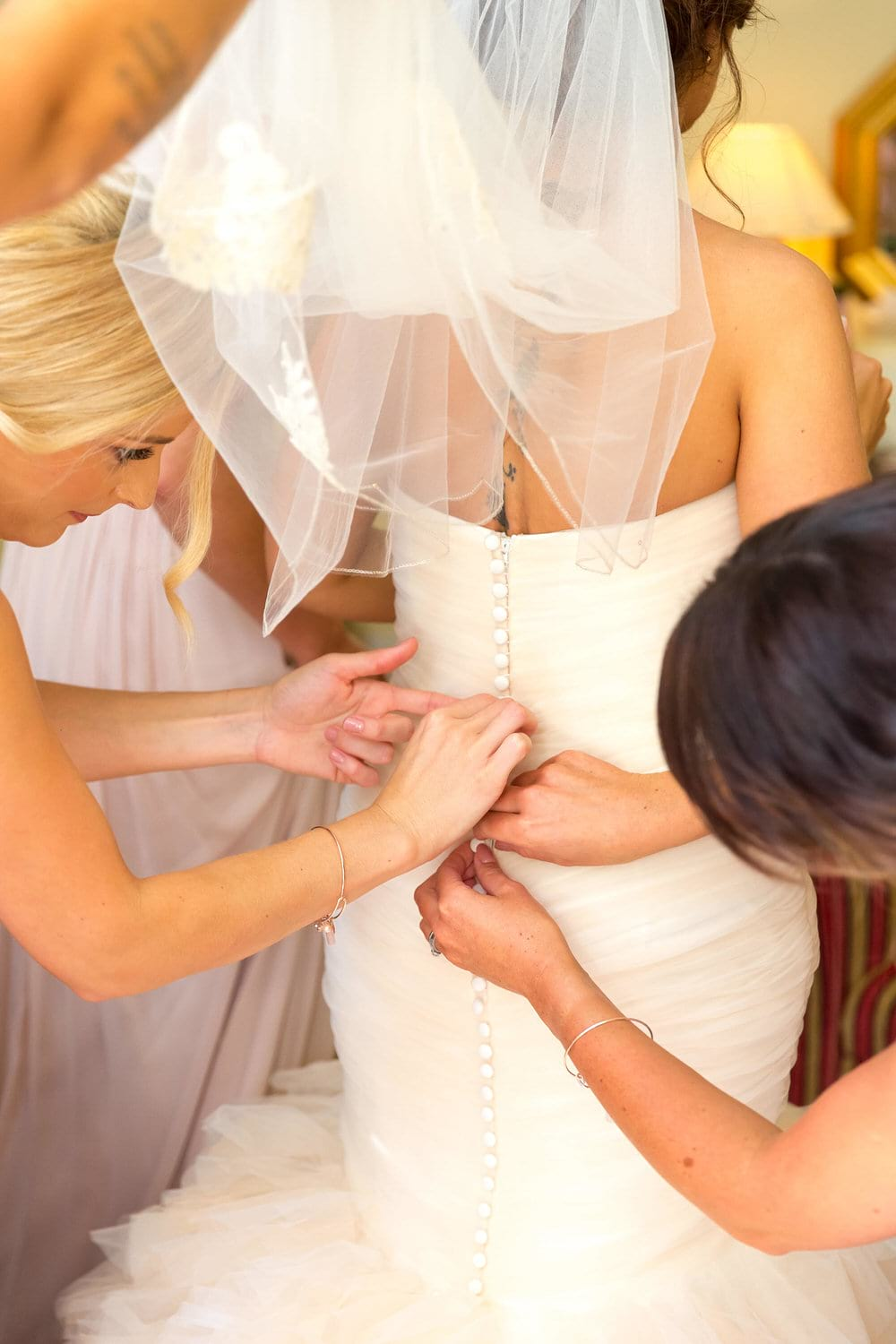 bridesmaids tending to the wedding dress