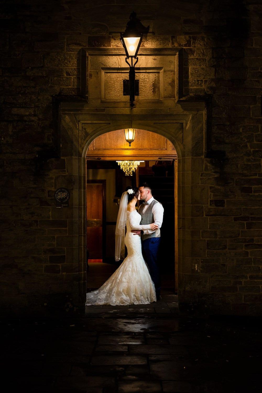 bride and groom kissing in doorway of bryngarw house