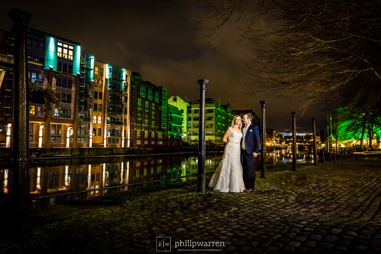 bride and groom by river in bristol at night