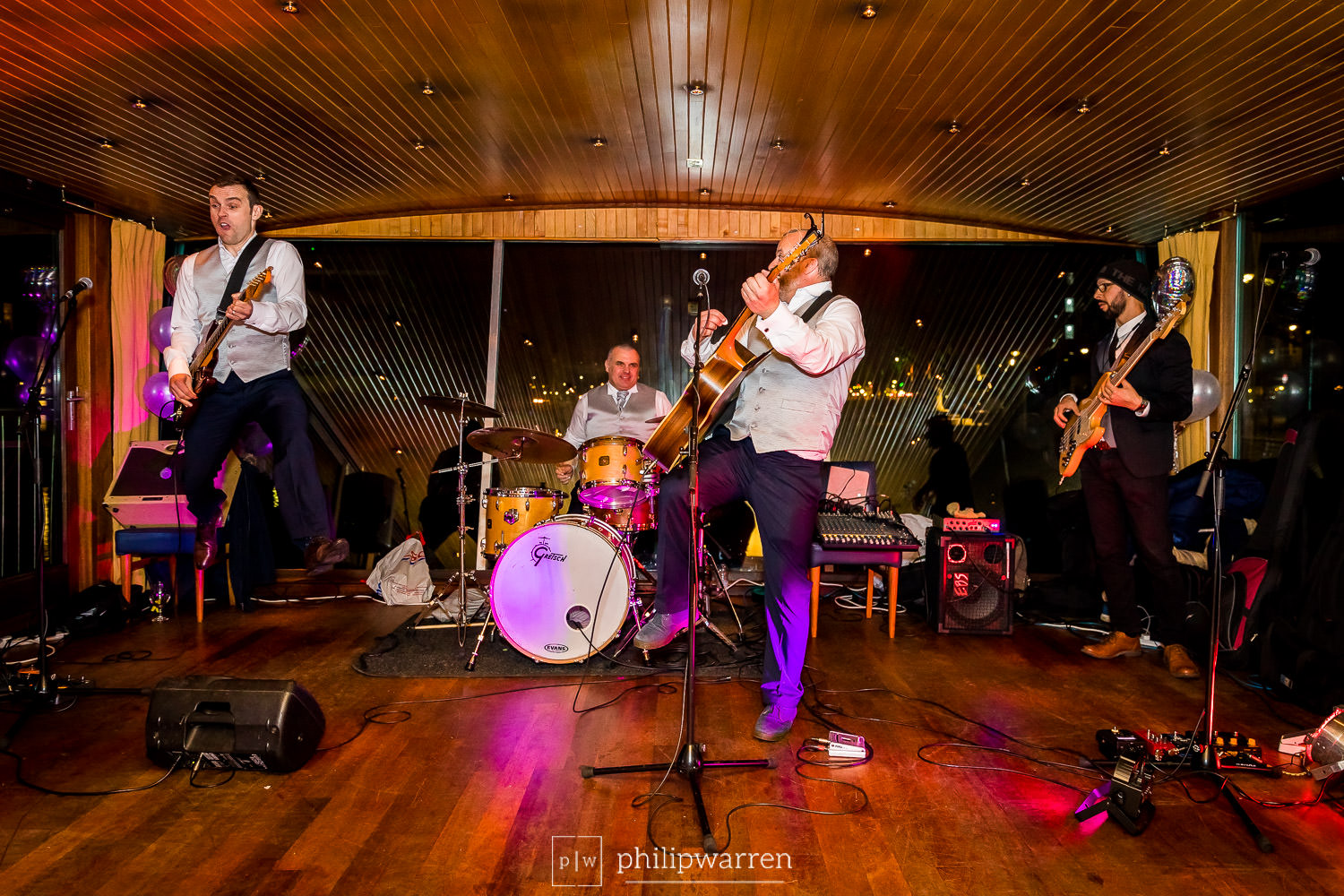 groomsmen playing as band with groom jumping in the air