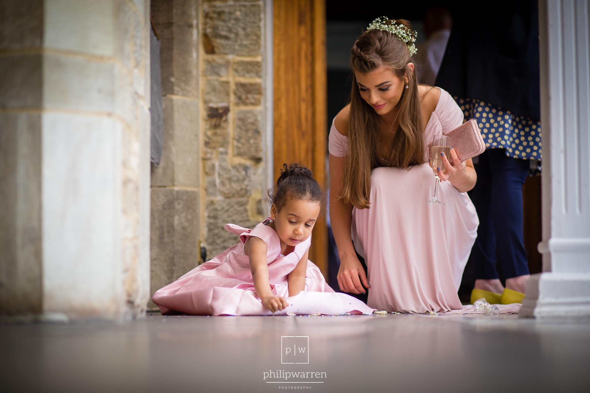 flower girl picking up confetti with bridesmaid