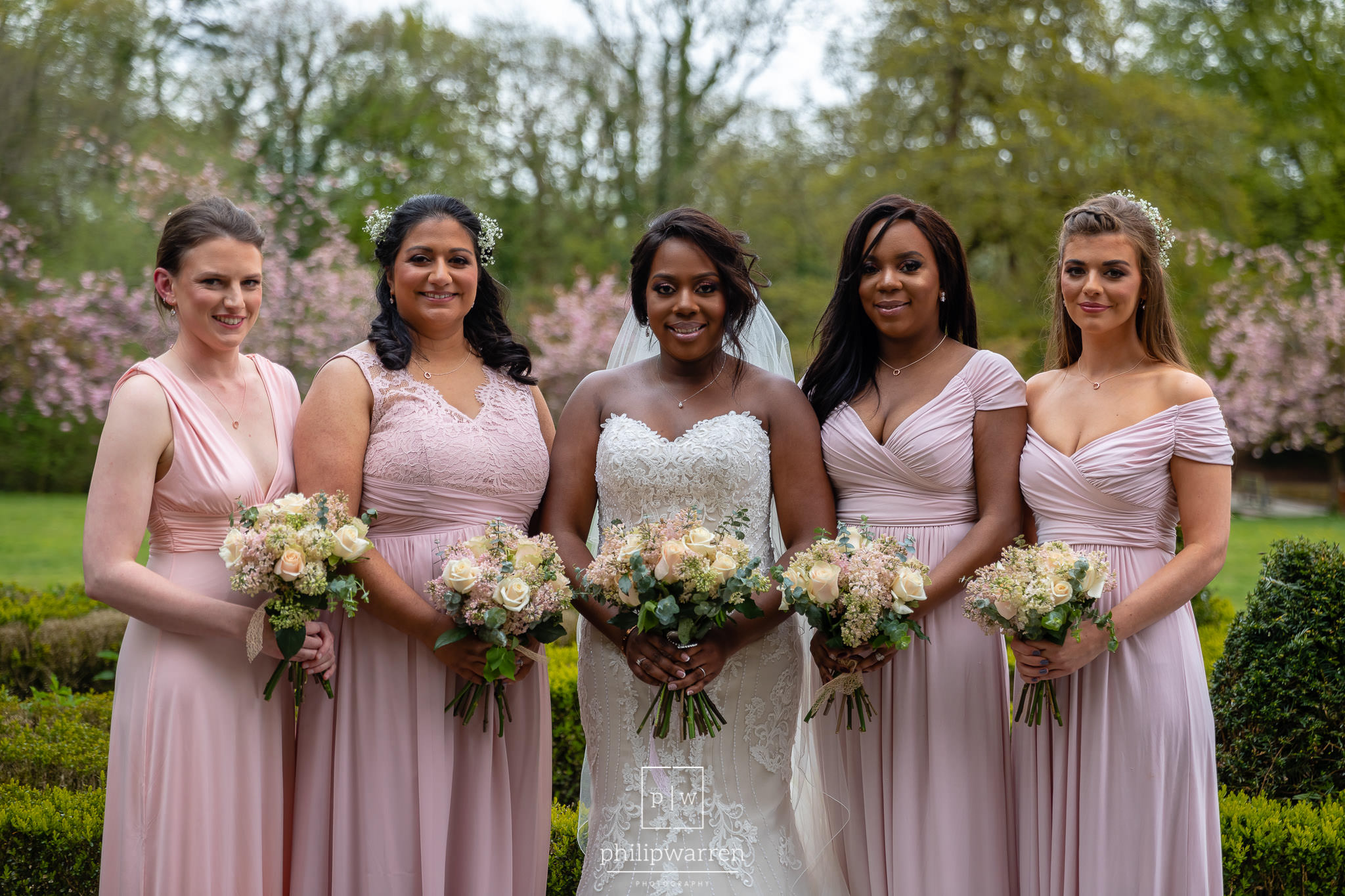 bride and four bridesmaids  holidng their bouquets