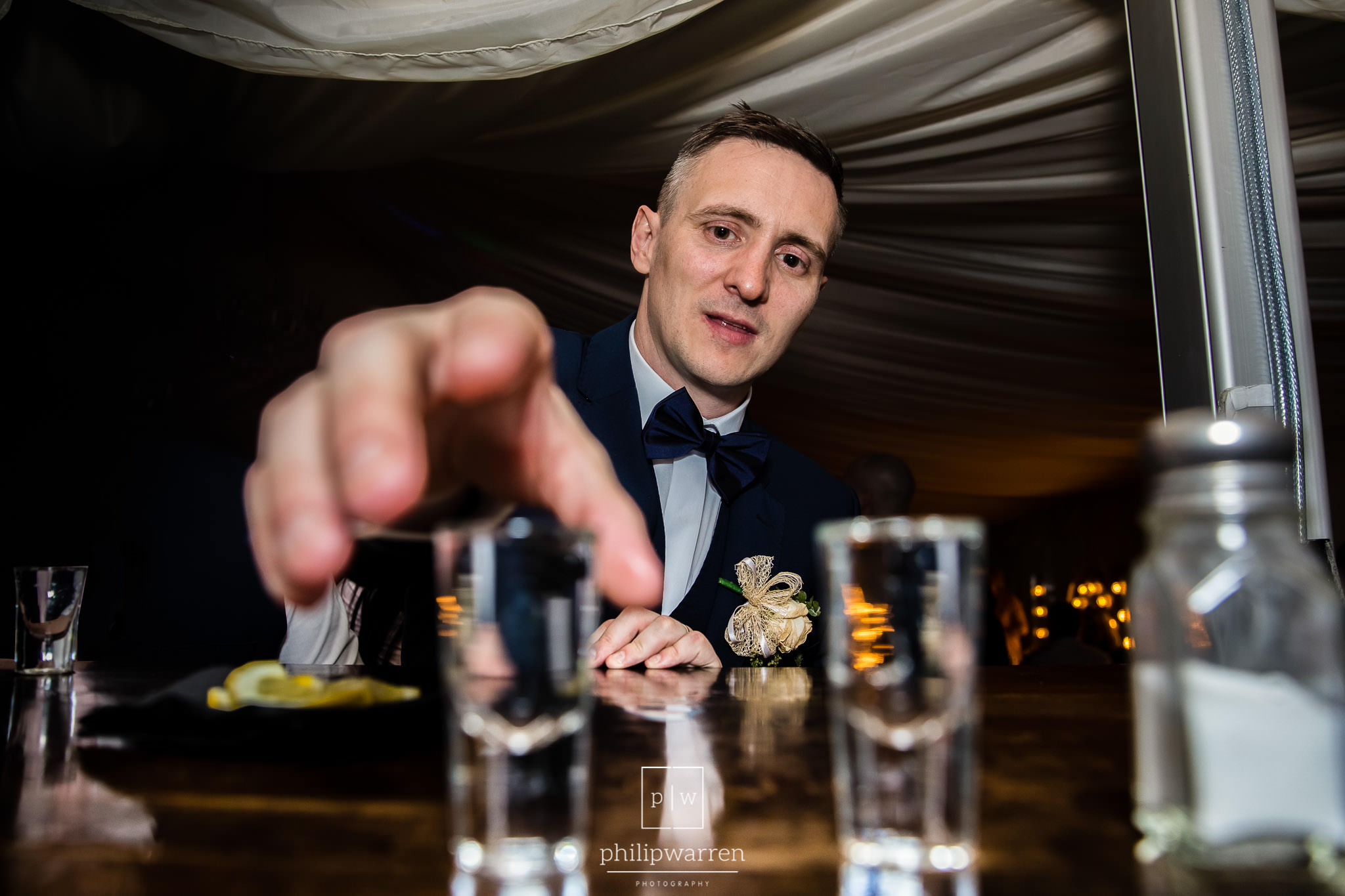 groom reaching for a shot of tequila at the bar in bryngarw hous