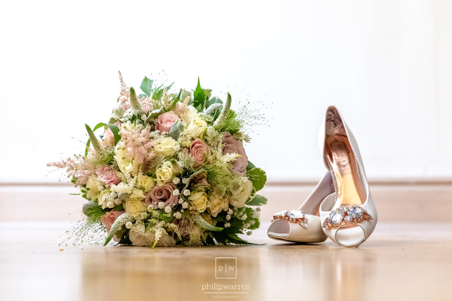 wedding bouquet and wedding shoes on wooden floor