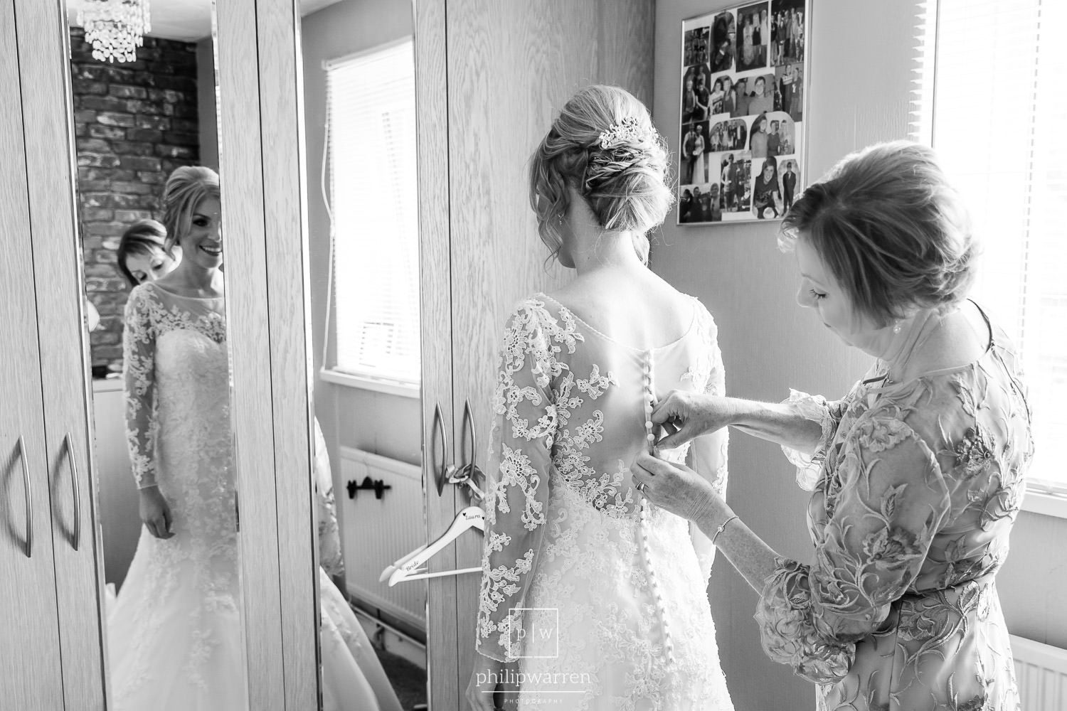 mother of the bride doing up the wedding dress