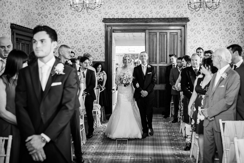 bride entering wedding ceremony with her dad