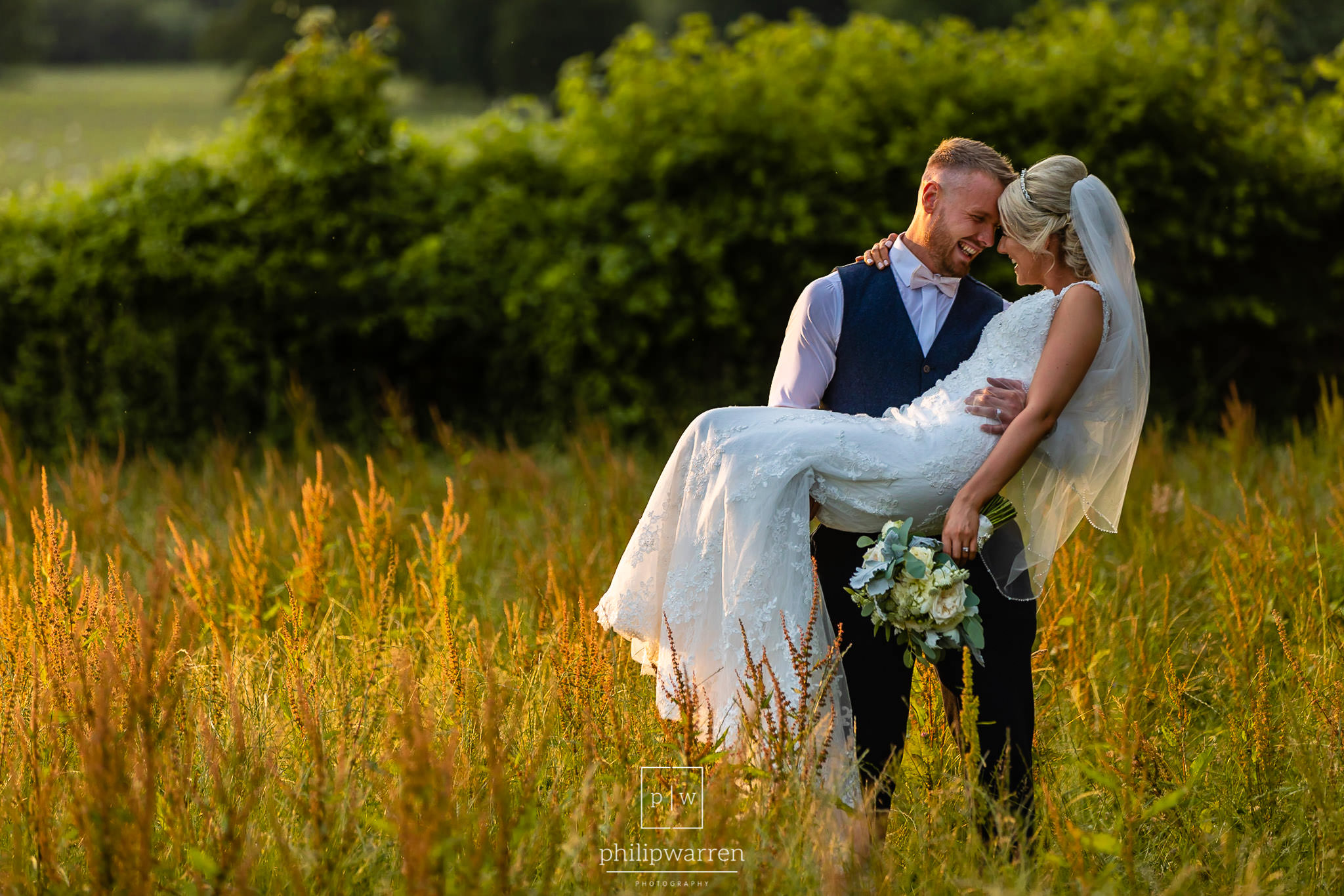 groom picking up bride standing in a field
