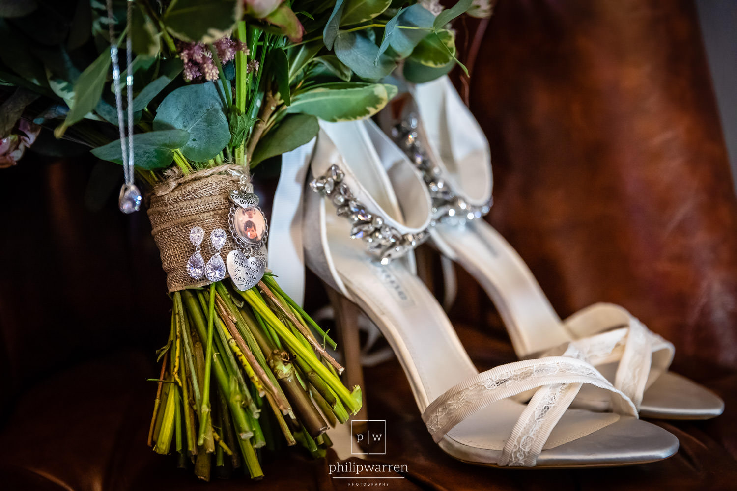 photo of the brides shoes jewellary and bouquet on leather chair