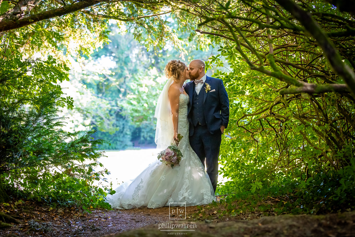 bride and groom kissing in the grounds of bryngarw house