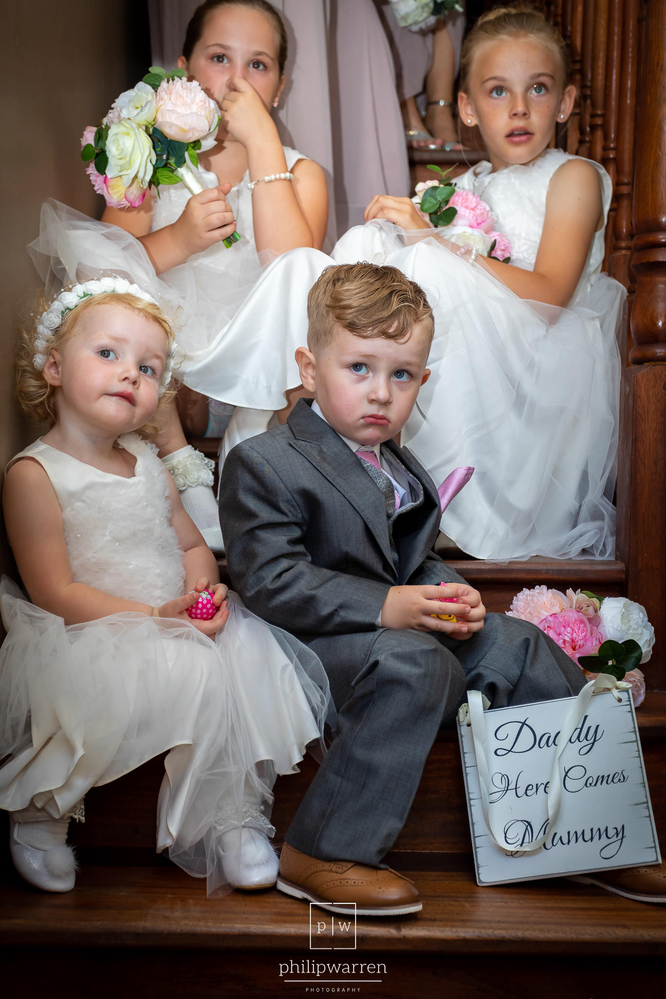 page boy and flower girls sitting on the stairs
