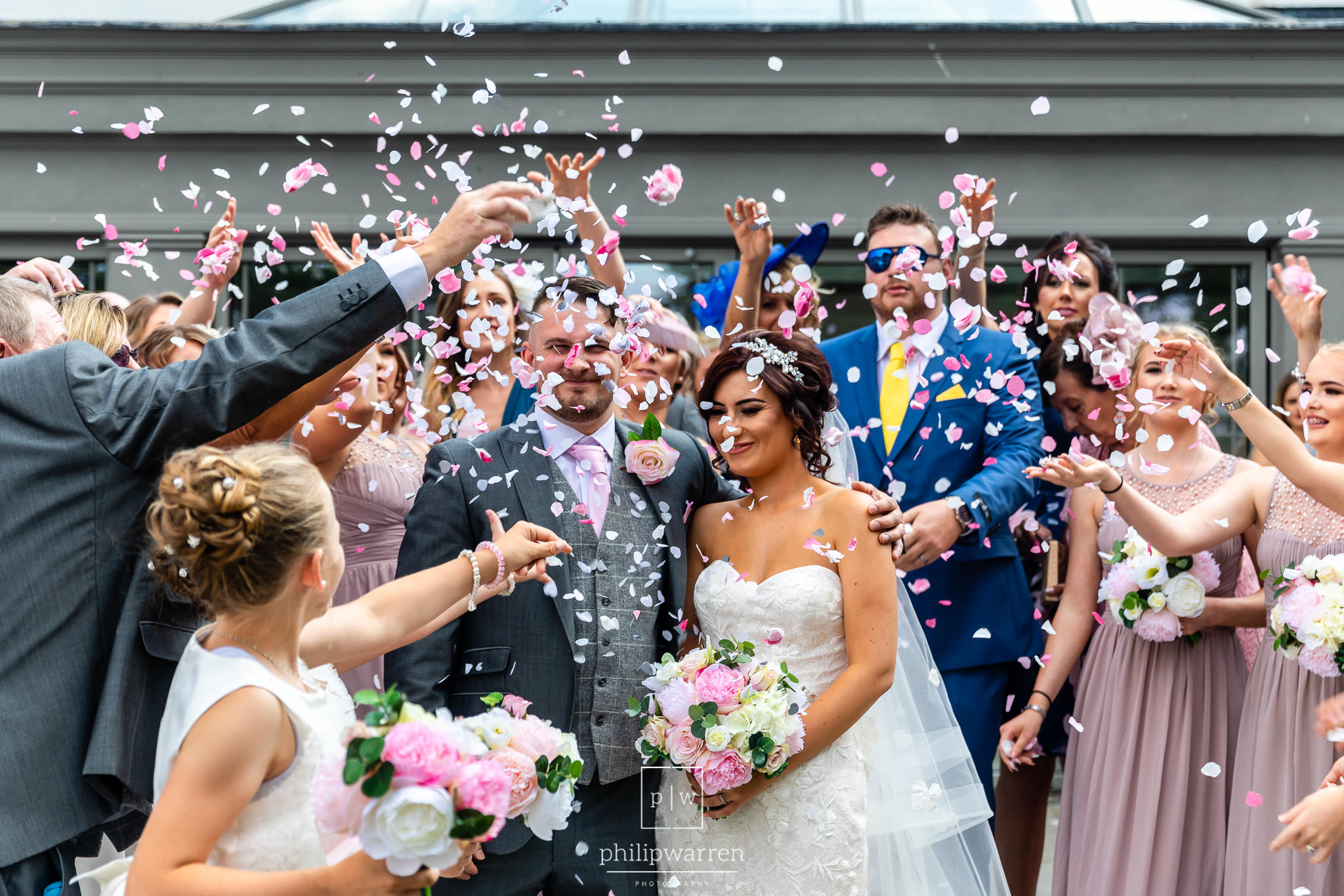 guests throwing colourful confetti at bride and groom
