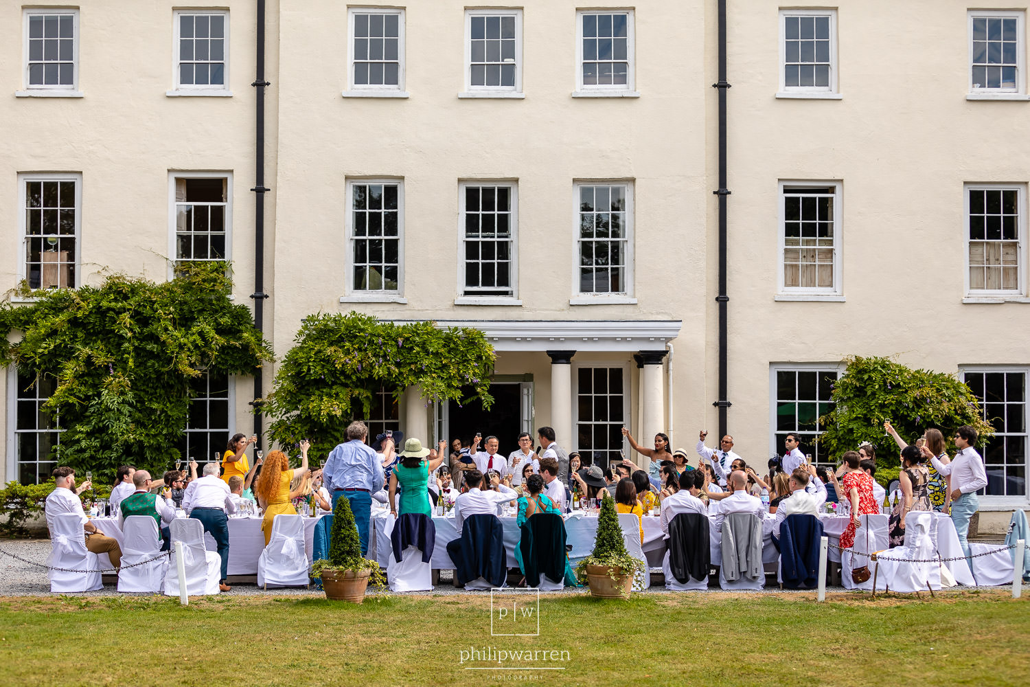 guests toasting the happy couple outside plas glansevin