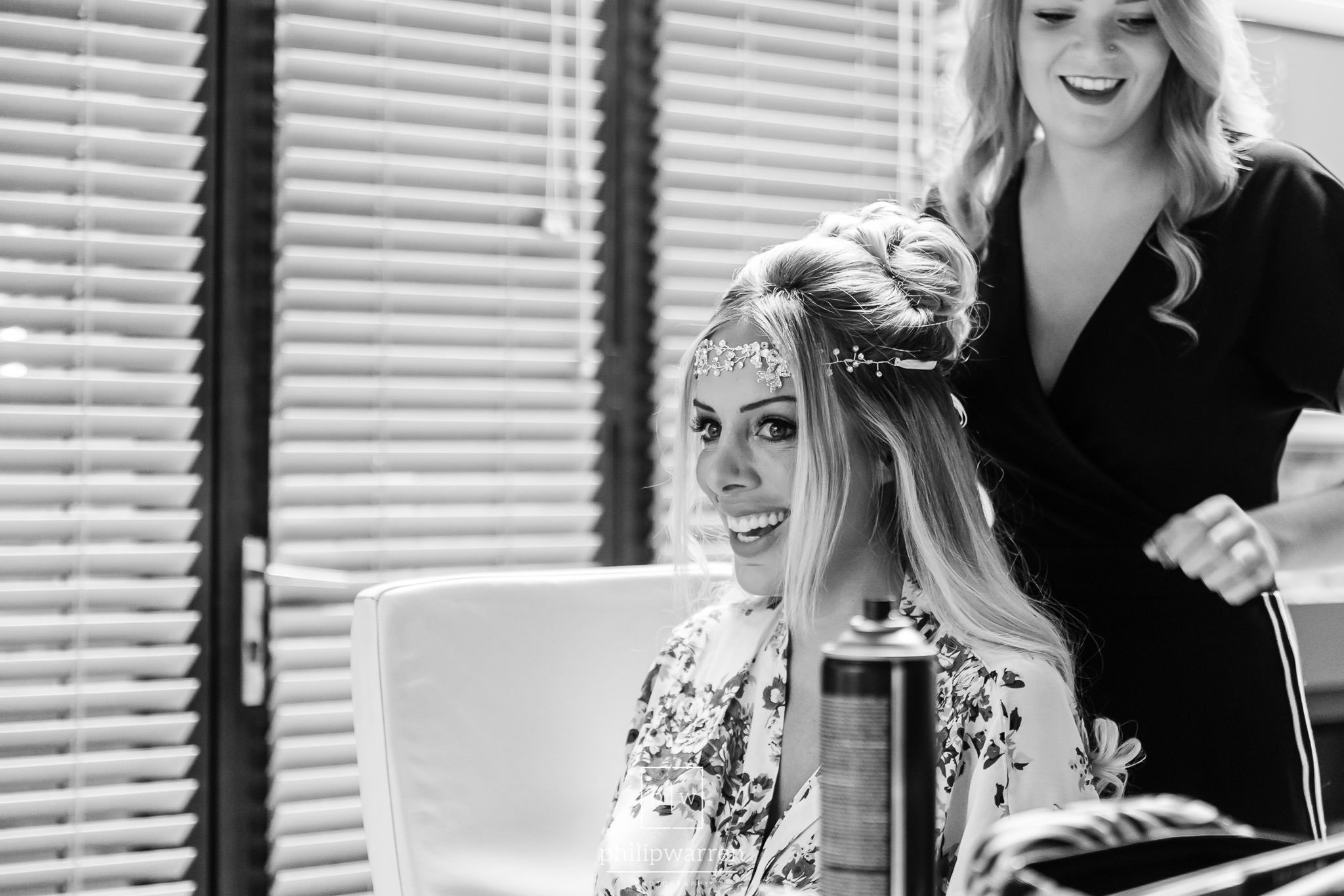 bride smiling whilst getting ready before wedding