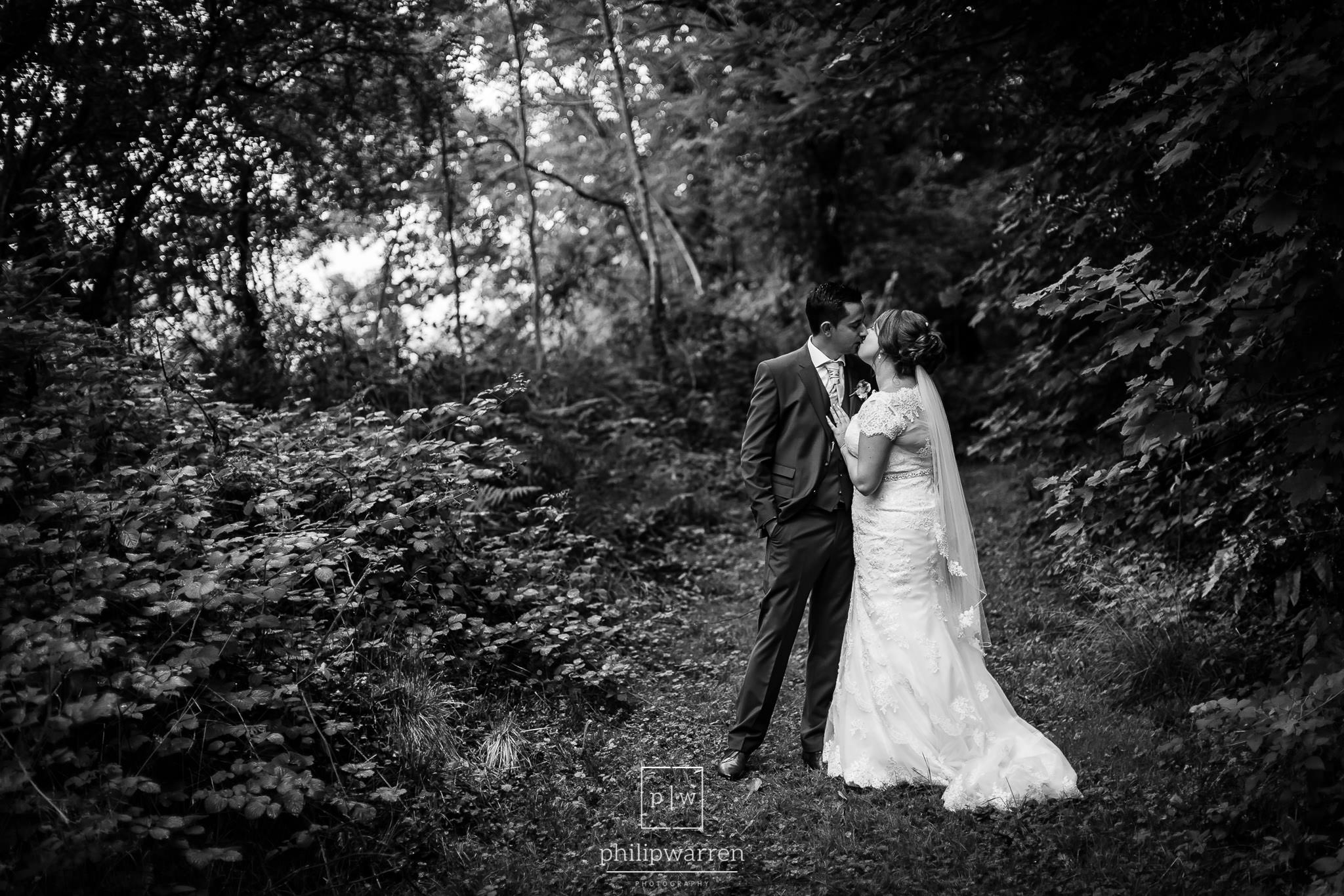 bride and groom kissing in the woods near new house country hote
