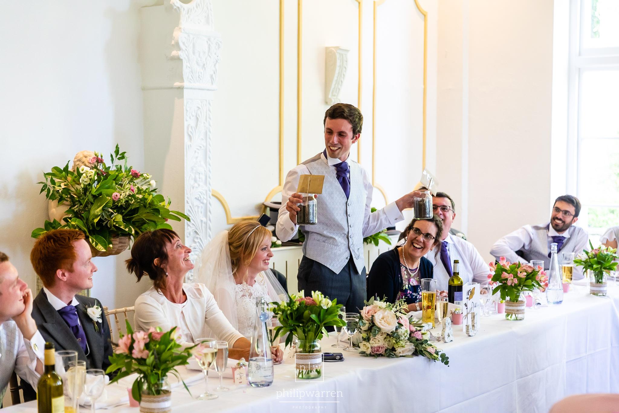groom presenting jars of dirt during wedding speeches