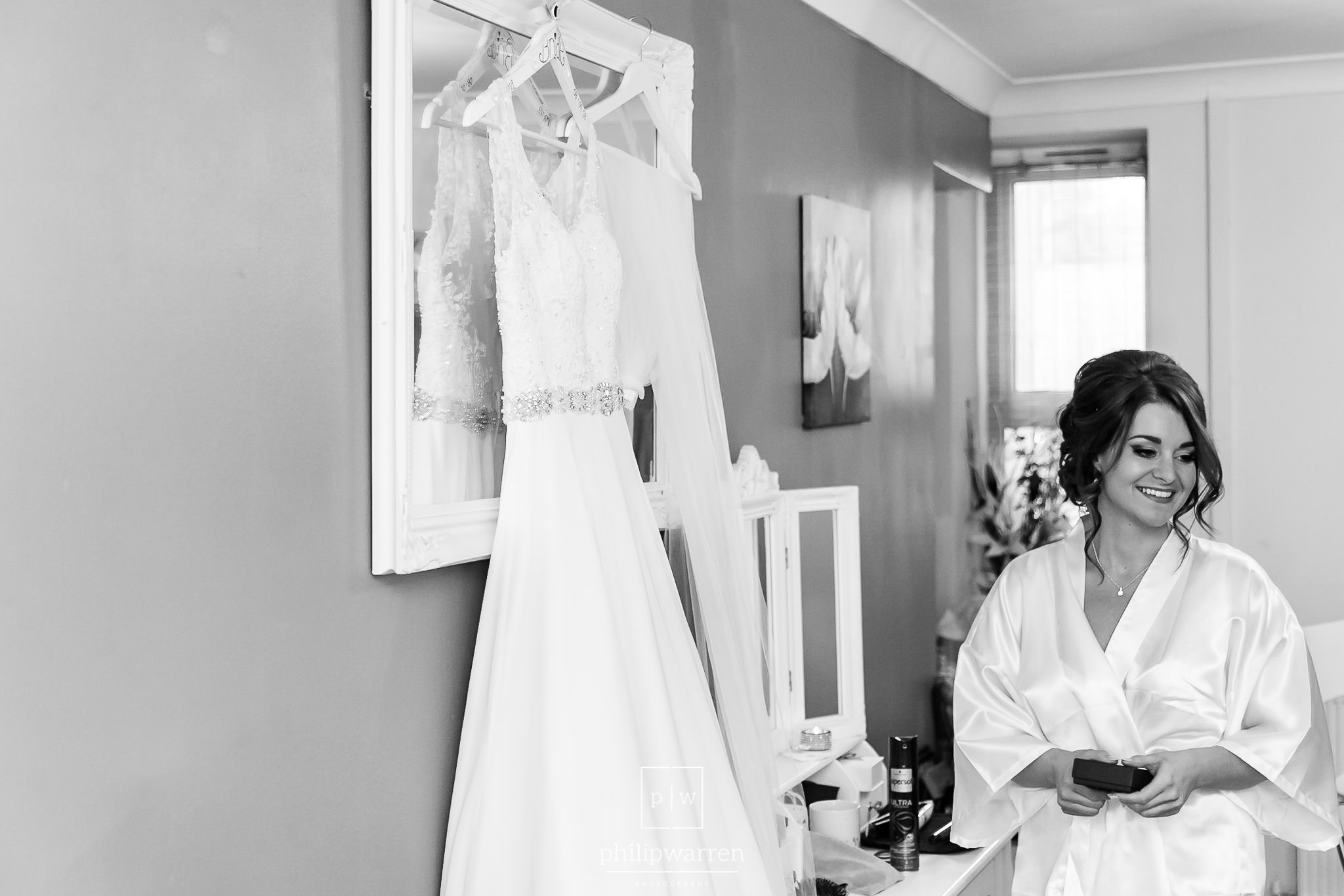 bride smiling by her wedding dress