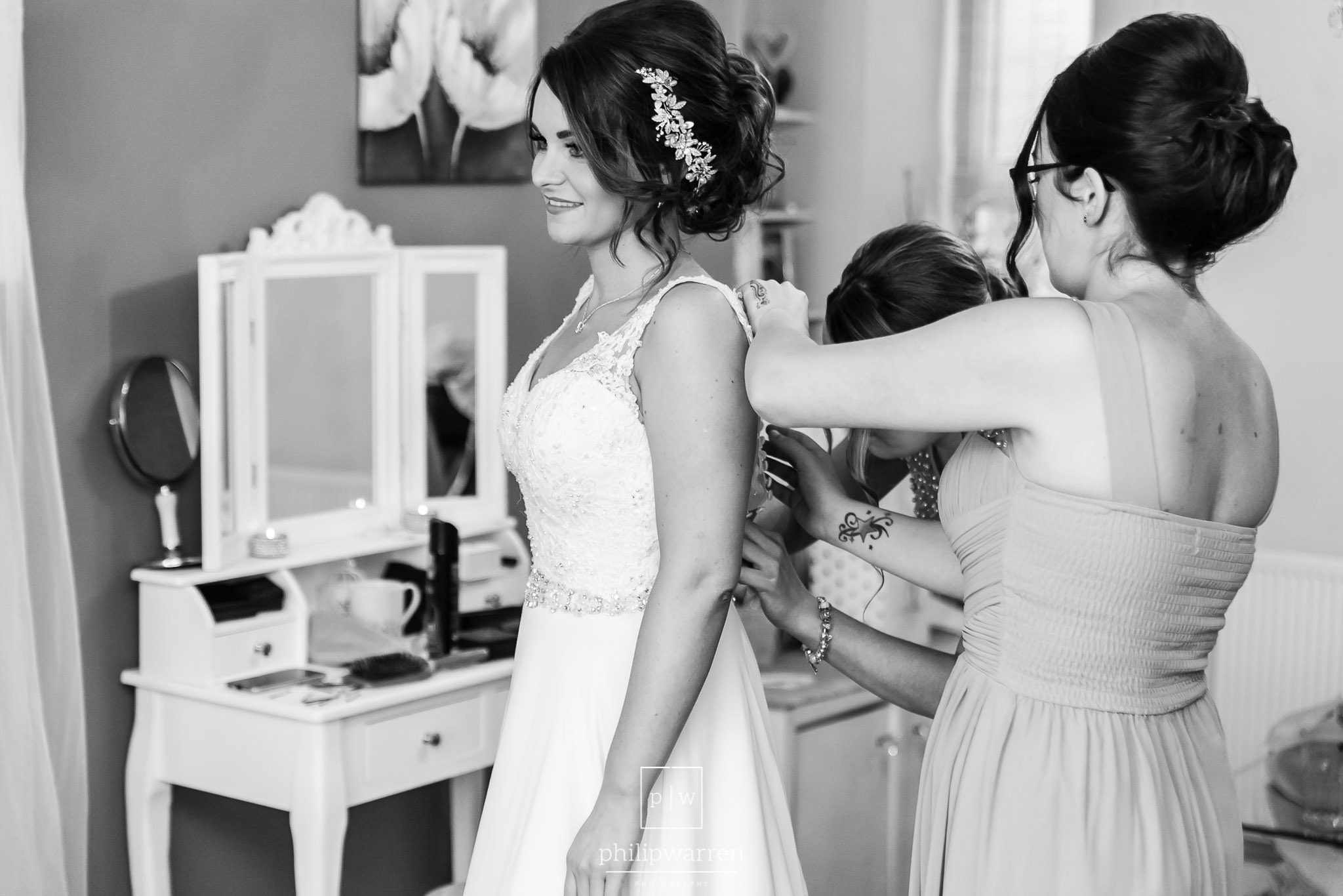 bridesmaids doing up the back of the brides wedding dress