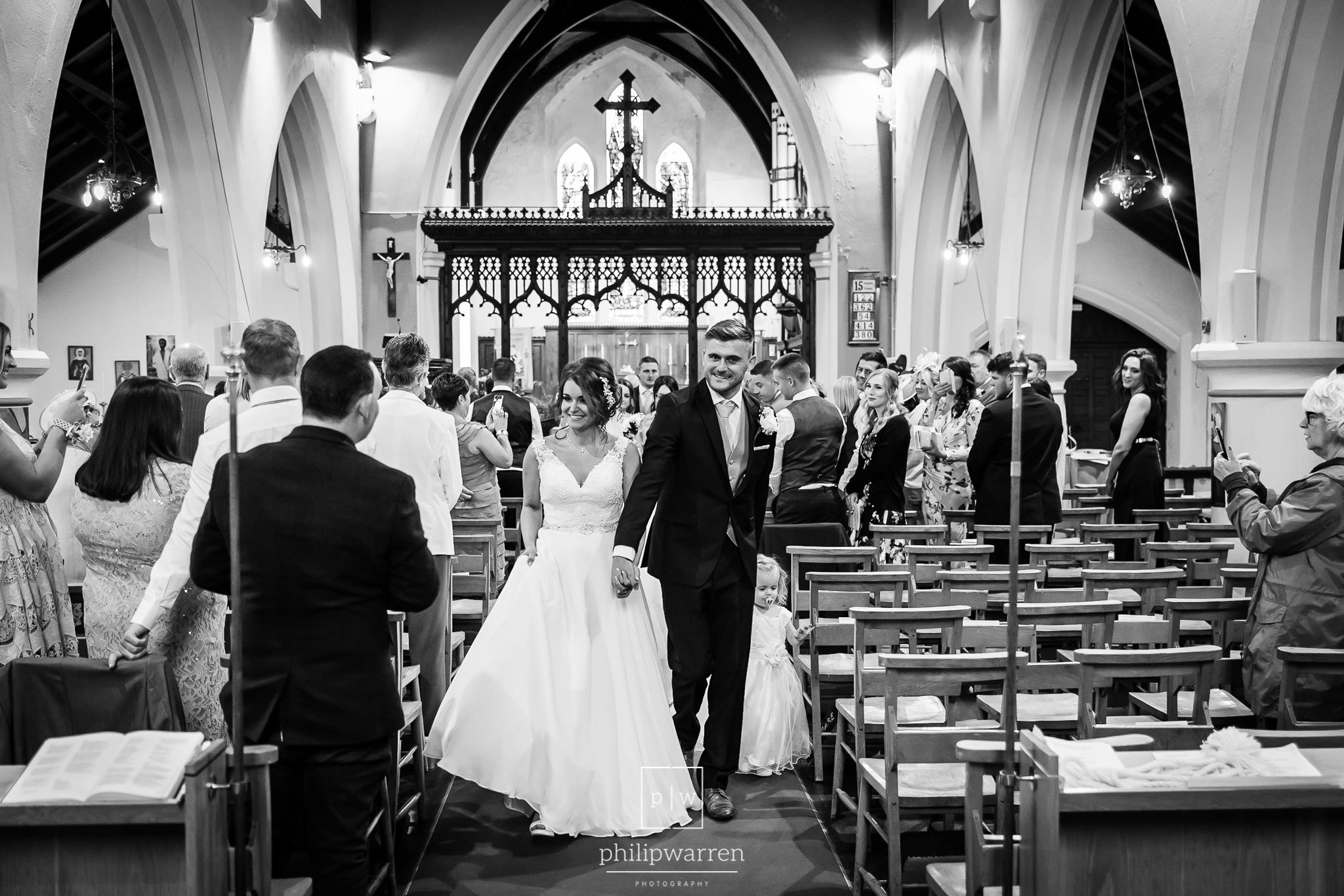 bride and groom leaving walking down the aisle in the church