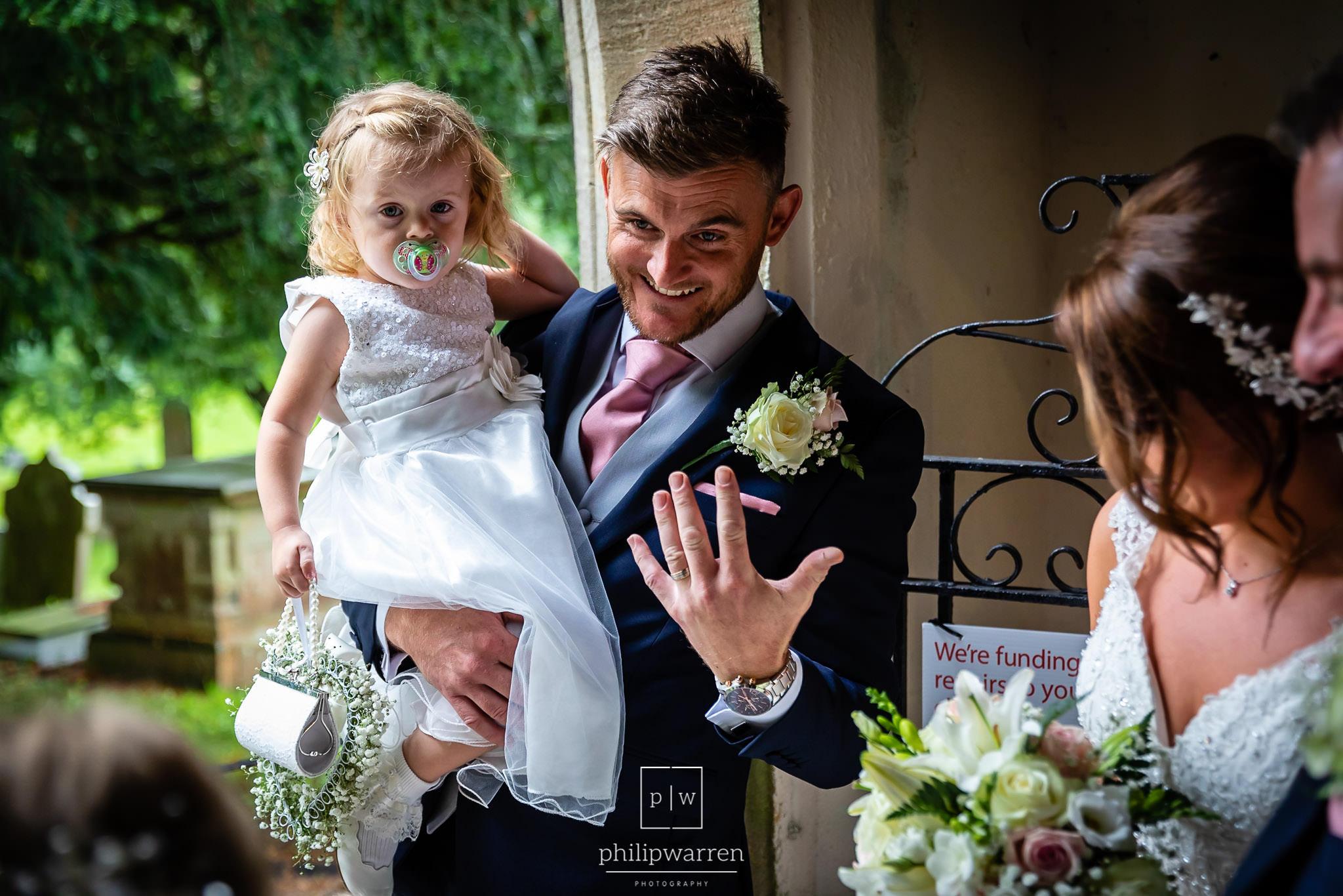 groom looking surprised at his new wedding ring