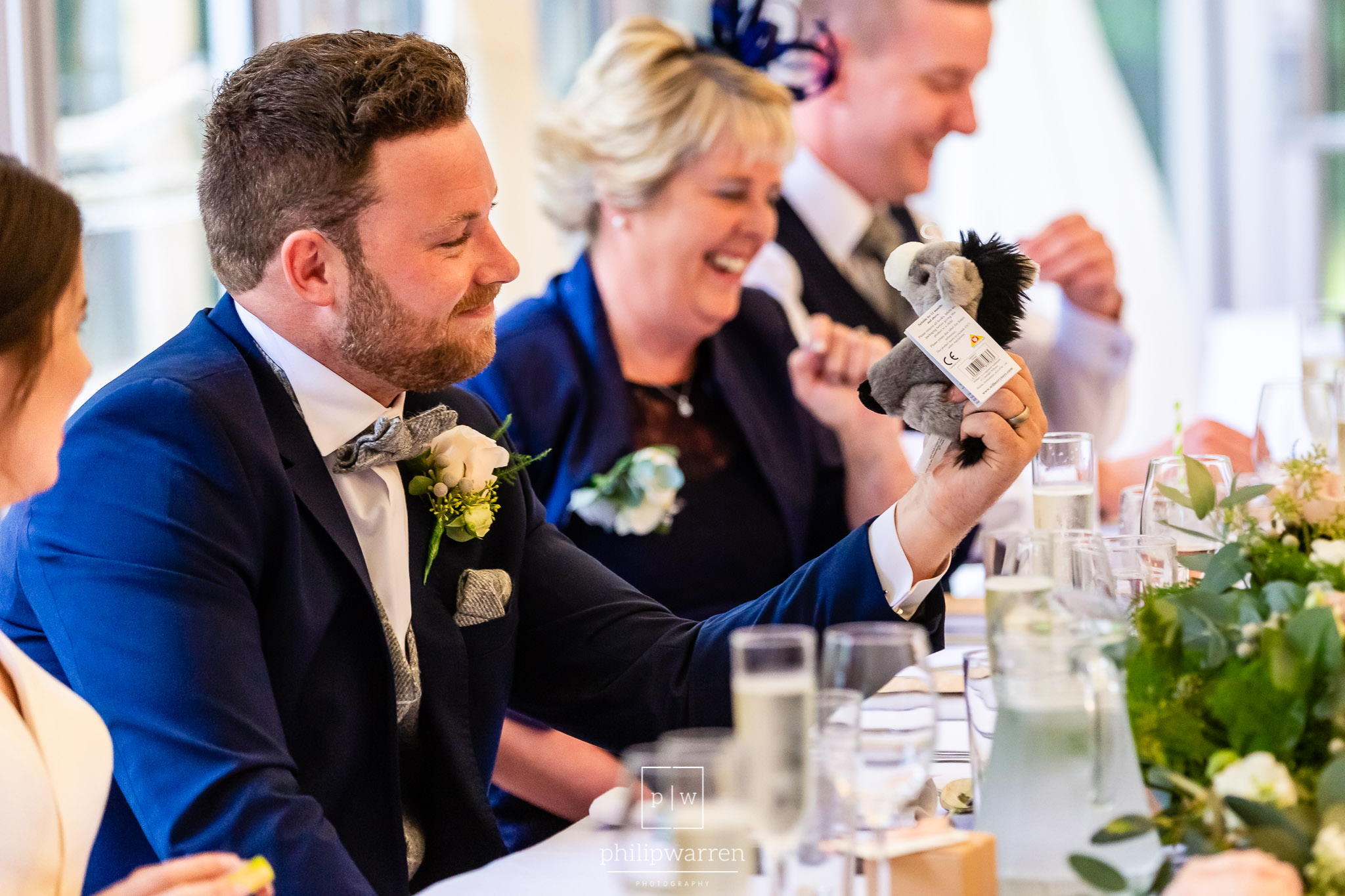 groom laughing at a stuffed toy during speeches
