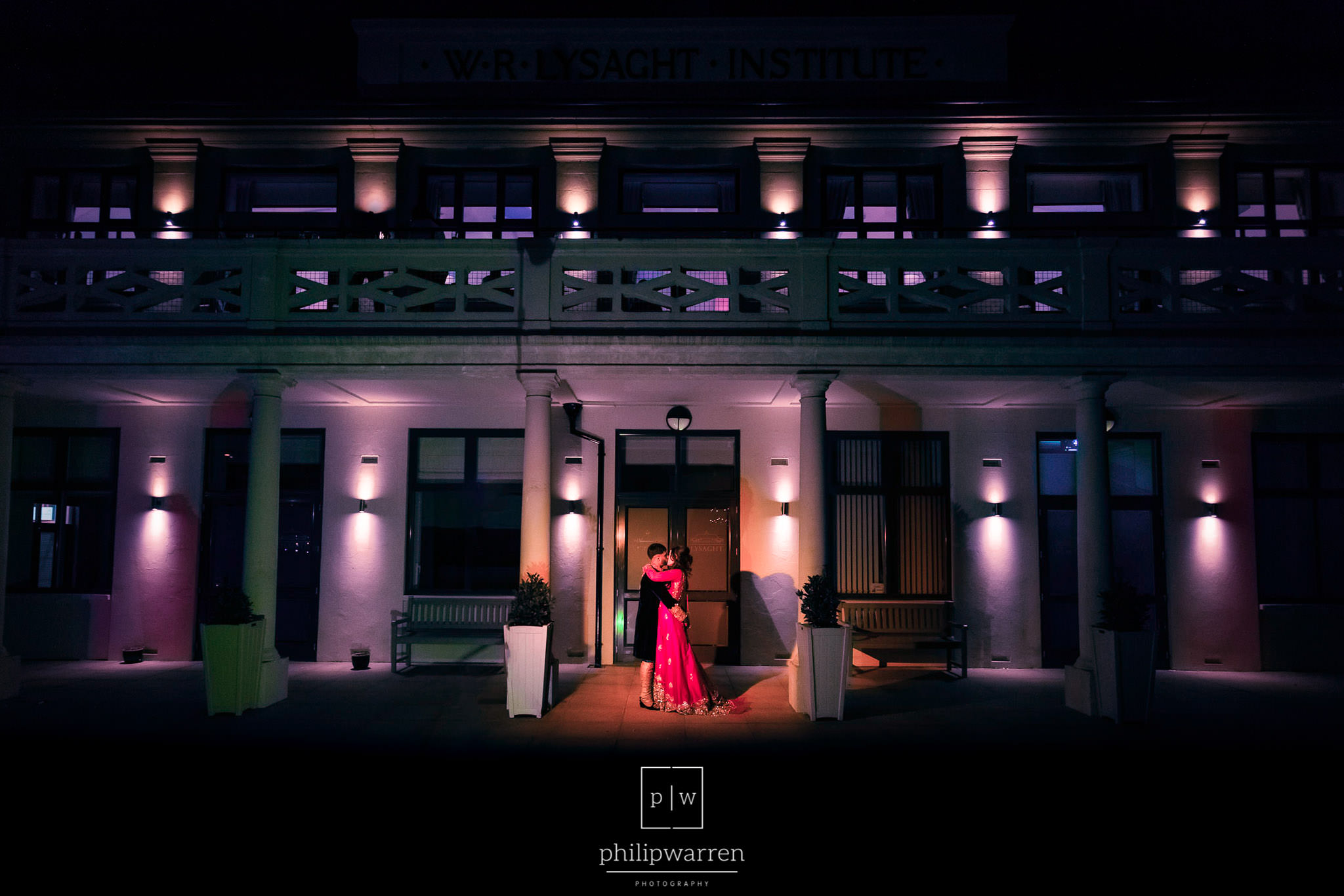 bride and groom standing outside lysaght institute at night