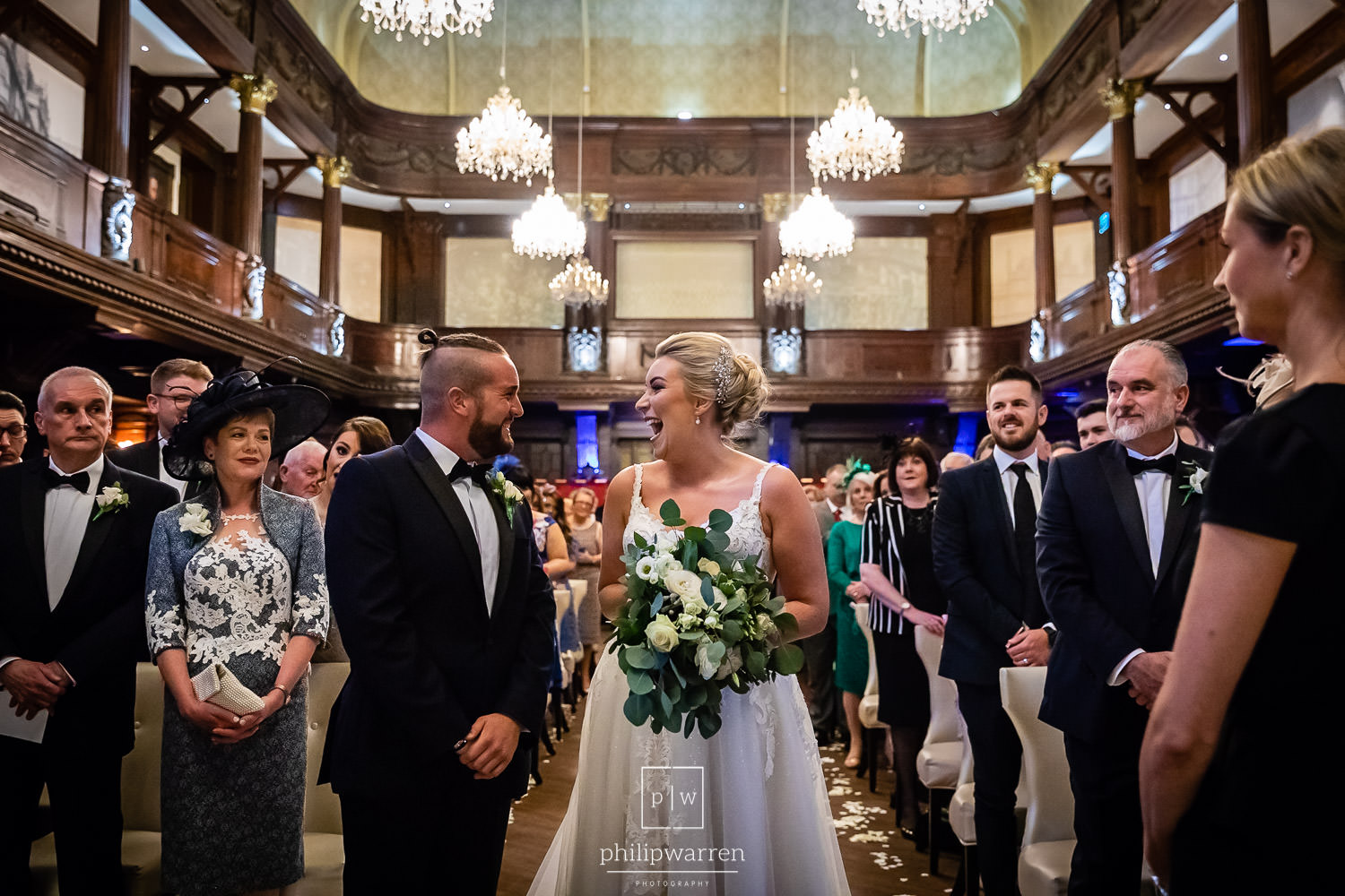 bride and groom laughing at each other during wedding ceremony