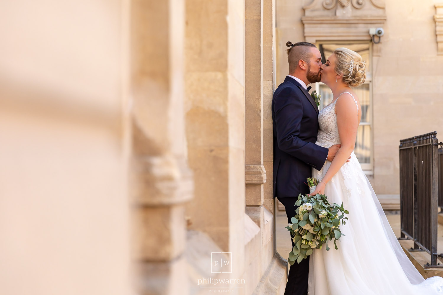 bride and groom kissing leaning against a wall