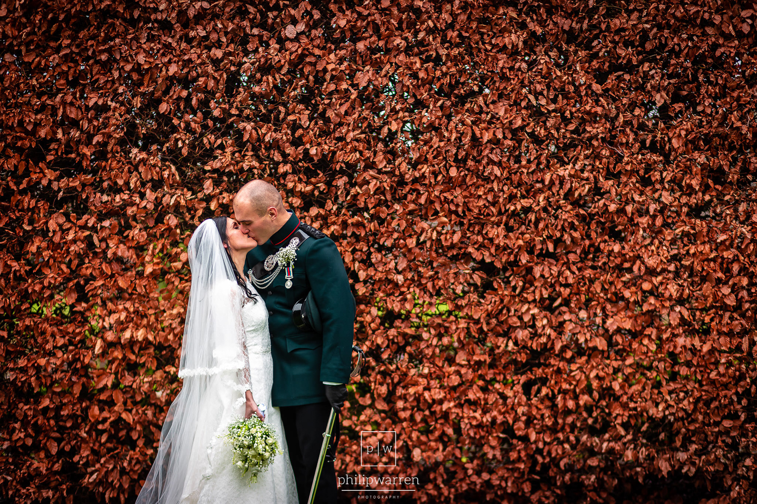 bride and groom kissing in front of orange bushes