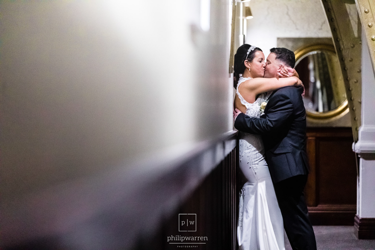 bride and groom kissing in the hallway