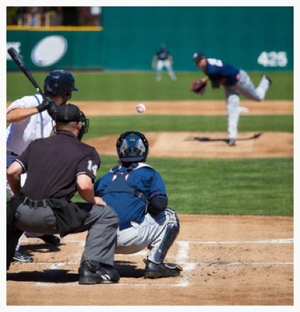 batter (left) in white uniform, umpire in black, catcher (crouching) in blue, pitcher (upper right) in blue.