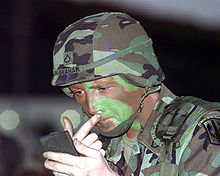 Here, a soldier wears camouflage gear and applies camo paint to his face. (source: Wikipedia)
