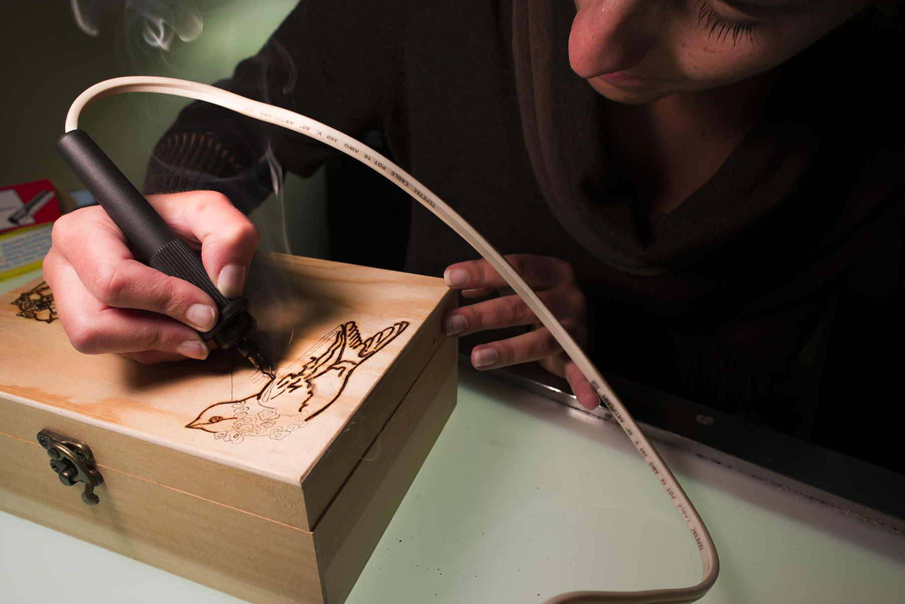 Julie Macala burning designs into wood, an art form known as pyrography | Columbus, Ohio