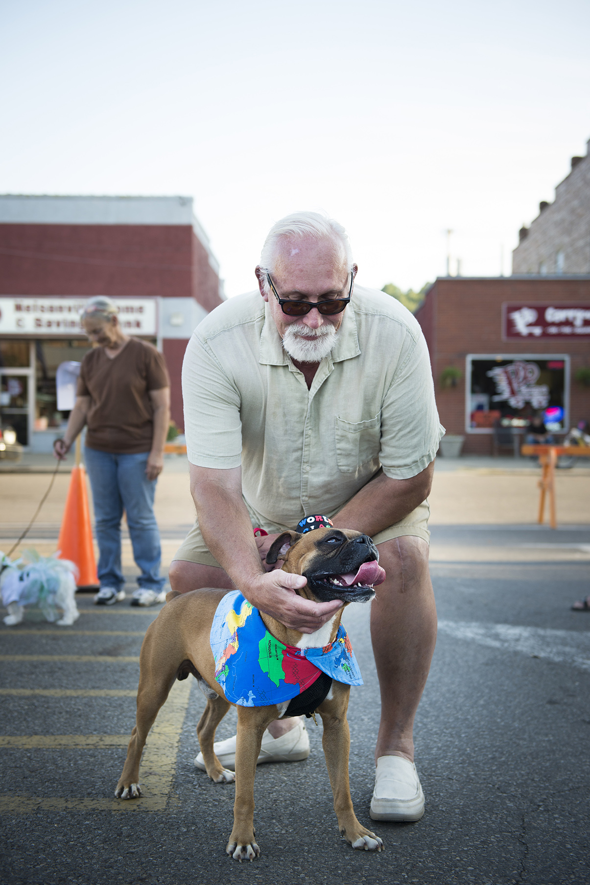 "Jim Addington and his miniature boxer, Louie, pose for a portrait on Friday, August 29, 2014 at the Final Fridays on the Square Dog Show in Nelsonville, Ohio.  Louie's costume reflects his life as a stray dog.  ""He's been all around the world,"" says Addington."