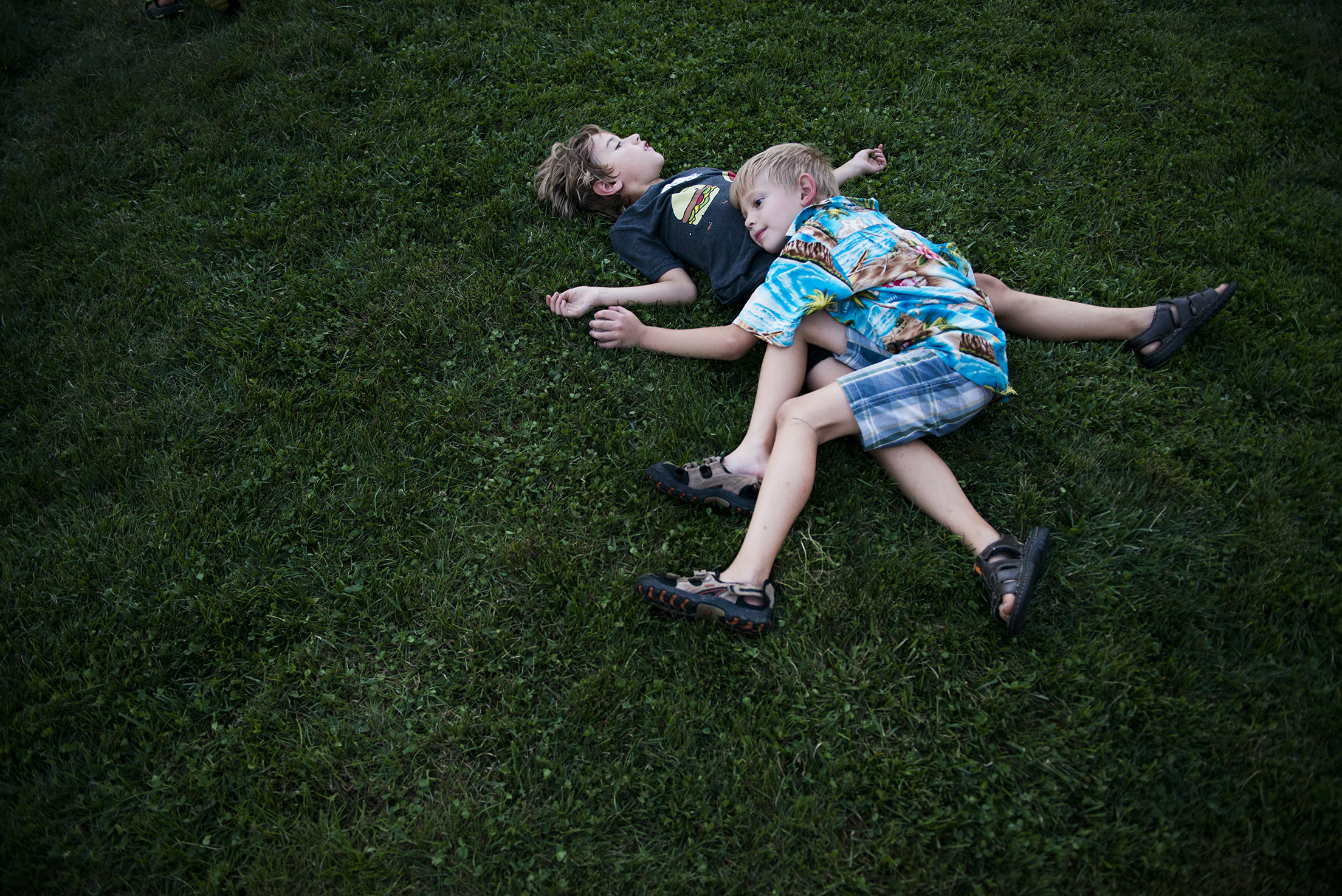 "Miles Makosky and Jonas Beasley, both 7, rest after wrestling together in the grass at Final Fridays on the Square in Nelsonville, Ohio on Friday, August 29, 2014. ""We're going to have a sleep over later,"" said Jonas."
