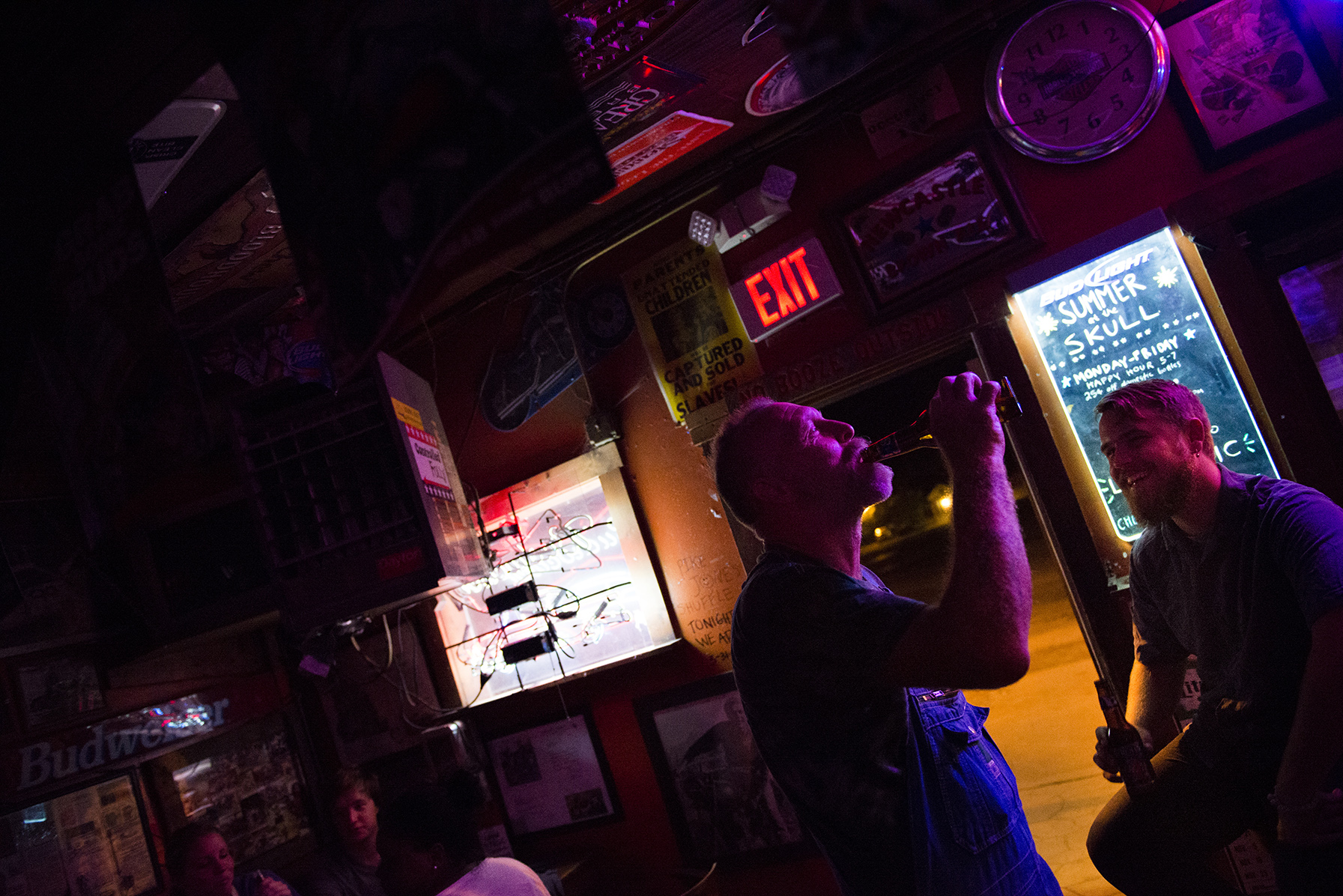 Earl Clark, a regular at The Skull, gulps down a beer on Friday, August 29, 2014 in Athens, Ohio.