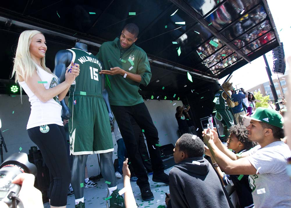 Giannis Antetokounmpo, #34 for the Milwaukee Bucks, poses with the new jerseys while fans take photos on Saturday, June 6, 2015 during the unveiling.