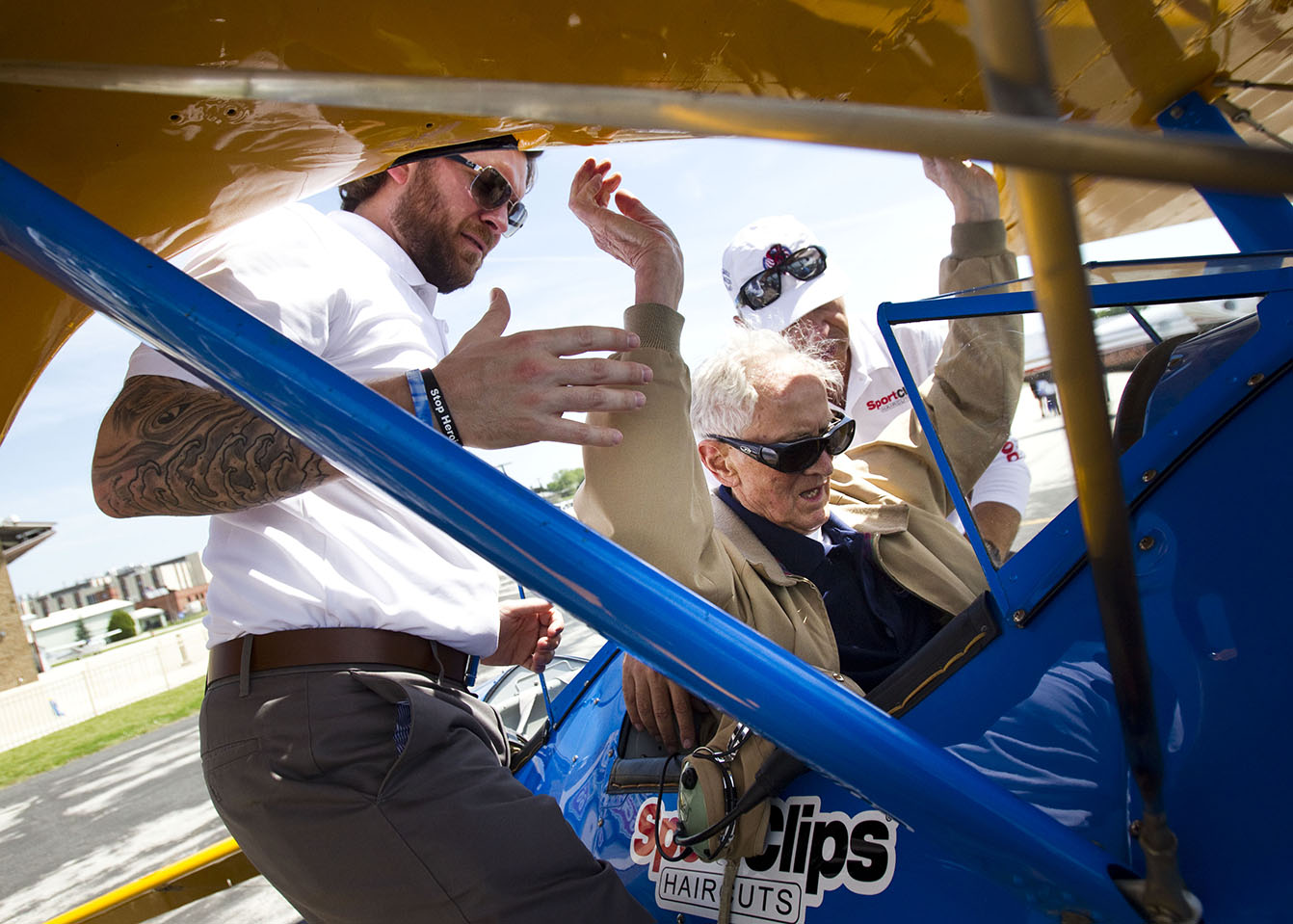 Steve Spokowicz, a 91-year-old Navy Veteran from World War II, slides into the seat of the Boeing Stearman biplane with the help of Jason Fritz (left) and Mike Sommars, the volunteer pilot with the Ageless Aviation Dreams Foundation, on Wednesday, June 10, 2015.