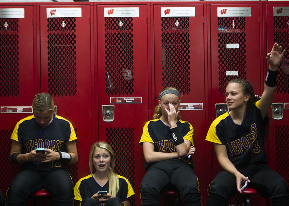(From left to right) Aly Otteson, Ciara Schwarz, Molly Annen, and Makenna Rauls, member of the Deforest Norskies, chat with teammates and check their phones while waiting for the rain to die down on Thursday, June 11, 2015 at the Goodman Diamond in Madison, Wis. The game was put on hold at the bottom of the second inning due to rain and the teams were ushered into the locker rooms to wait for it to stop.