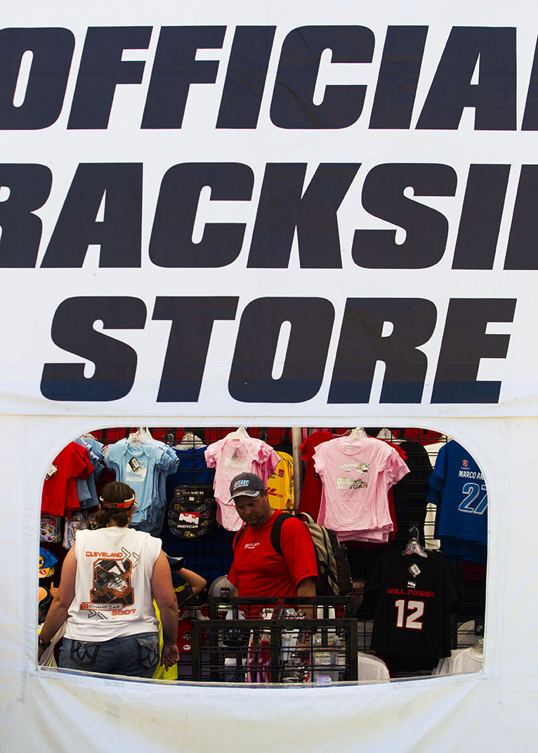 Festival goers browse through the merchandise available in the Official Backside Store on the infield during Indy Fest on Sunday, July 12, 2015.