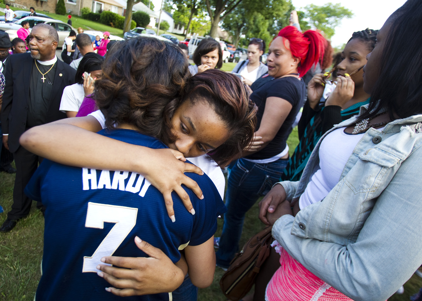 Kimberly Smith, 15, hugs her friend, Swanessey Covington-Juarez after the vigil to celebrate the life of Tariq Akbar.  Smith and Covington-Juarez were friends of Akbar.