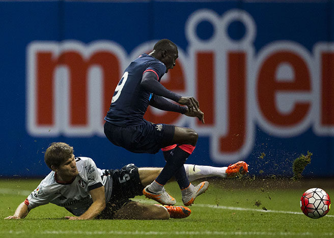 Walter Kannemann, defender for Club Atlas, slide tackles Papiss Cissé, forward for Newcastle United, during the Newcastle United vs. Club Atlas game at Miller Park on Tuesday, July 14, 2015.