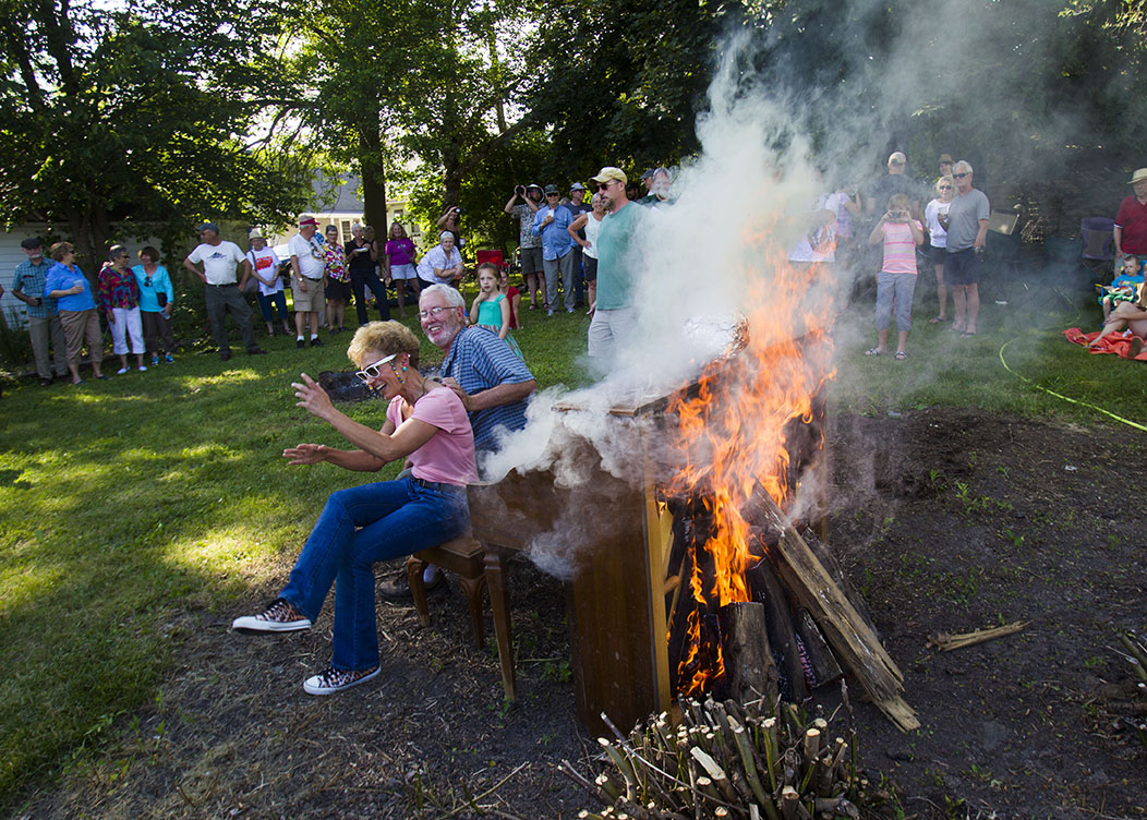 Ellen Tsaloff and Dan Johnson sit next to the burning piano for a photo on Sunday, June 21, 2015 at the Roxbury Tavern in Sauk City, Wis. The tradition at the tavern started over eight years ago.