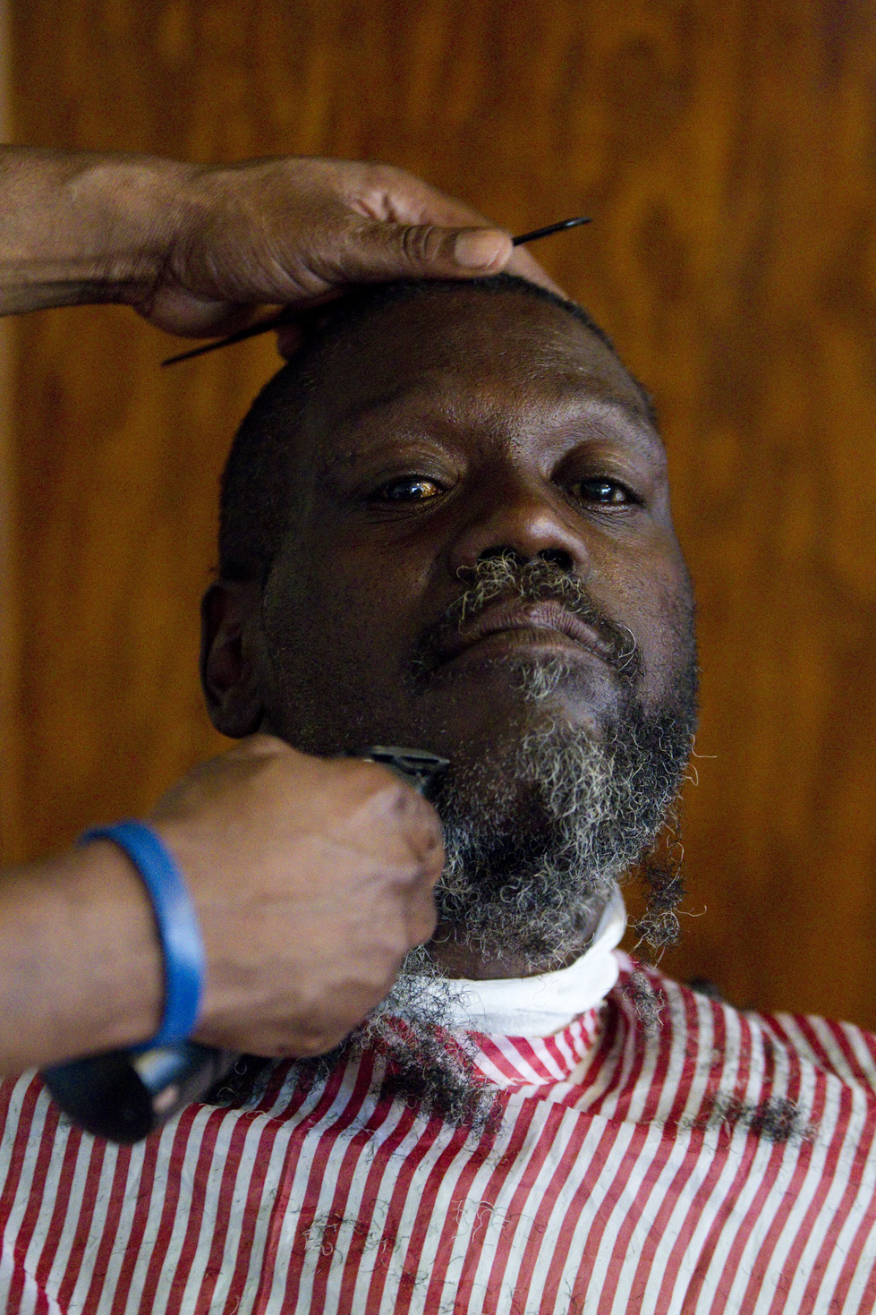 John Toney, a barber at Uppercuts, gives Charles Cotton a free haircut as a part of Barbershop Mondays on Monday, July 14, 2015.  Damien Smith, a youth organizer for Safe and Sound, leads inter-generational conversation around different topics each week while attendees get their hair cut. This week's topic revolved around family structure.