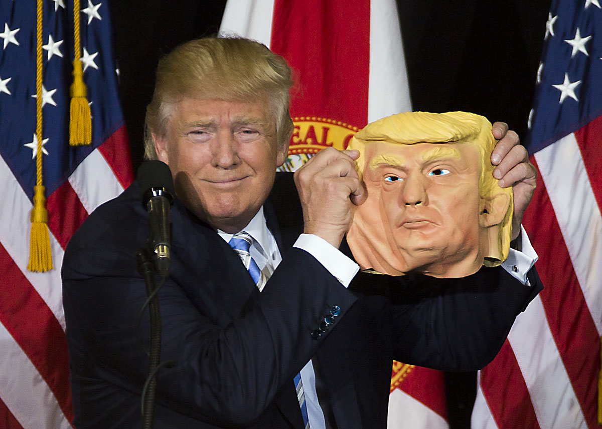 Republican candidate Donald Trump holds up a mask of his face during his speech at Robarts Arena on the Sarasota fair grounds on Monday, November 7, 2016 in Sarasota, Florida.