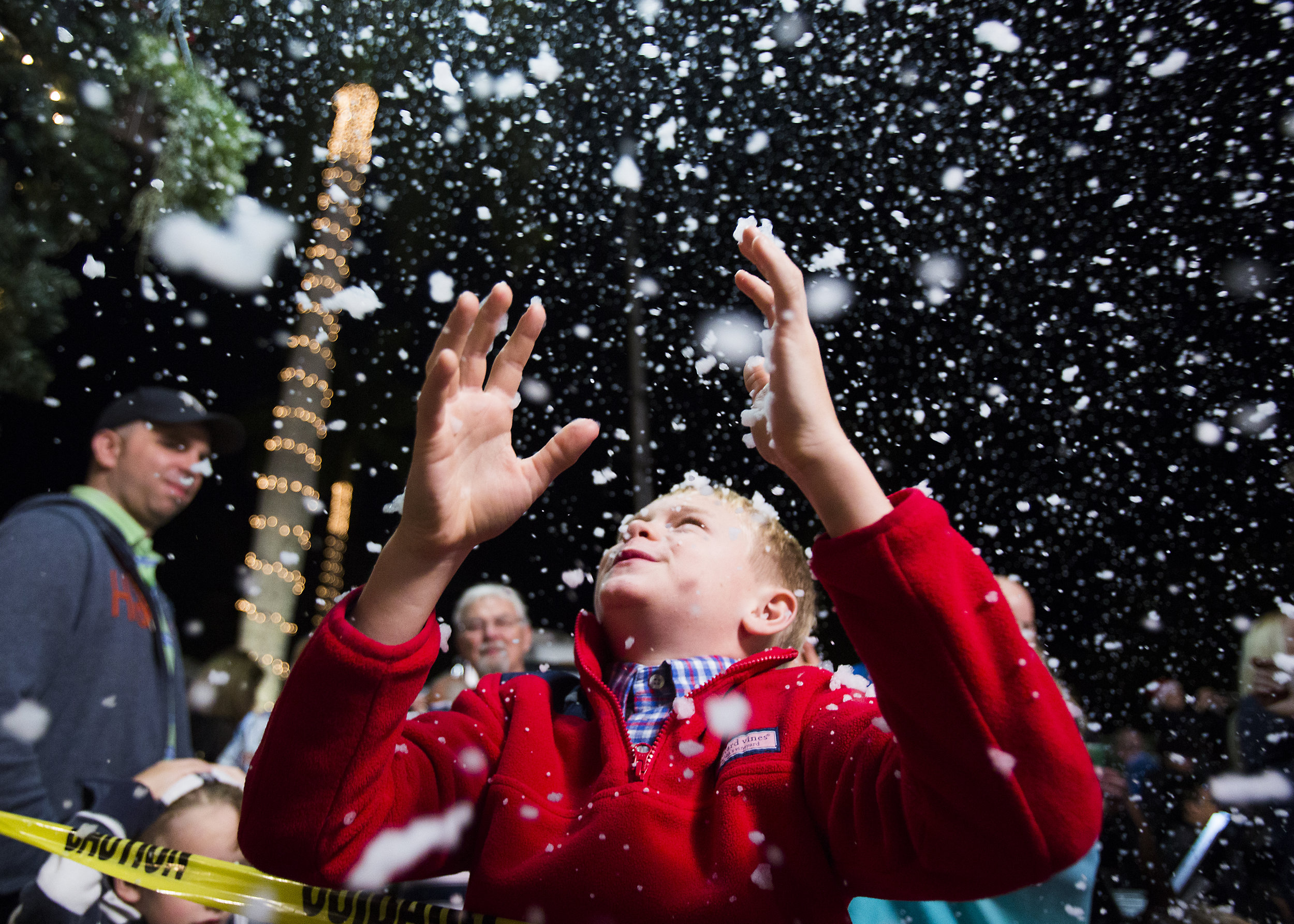 "Will Kramer, 9, looks up towards the ""snow"" during the annual Christmas on Third celebration in downtown Naples on Monday, November 21, 2016. The event featured tree lighting, ice sculptures, music and fake snow."